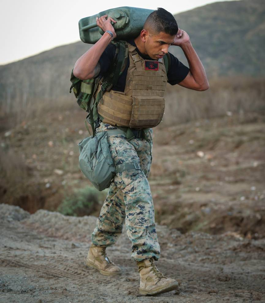 December 11, 2019 - U.S. Marine Gunnery Sgt. Freddy Torres, the chief instructor for Corporals Course 1-20, Headquarters and Service Company, Headquarters and Support Battalion, Marine Corps Base Camp Pendleton, carries a water jug during a physical training session on Marine Corps Base Camp Pendleton, California. The PT session was designed to illustrate different tenets from the Marine Corps' doctrine on the nature of war, including friction, uncertainty and complexity. (U.S. Marine Corps photo by Lance Cpl. Andrew Cortez)