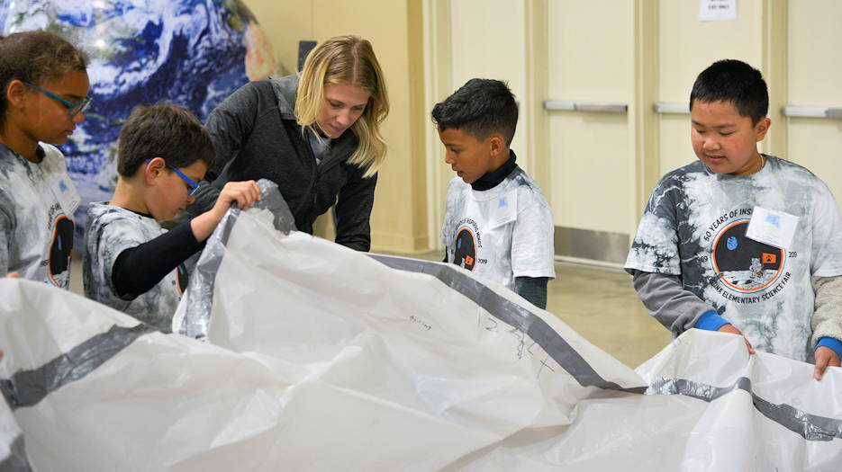 Tamara Torres and her students from Osuna Elementary inflate their habitat during the 2019 Mission to Mars at the Albuquerque Convention Center May 10th. The Air Force Research Laboratory New Mexico's STEM Outreach branch put on the mission, with more than 1,300 fifth-grade students from schools across the Albuquerque area and New Mexico taking part in the massive science and engineering experiment. (U.S. Air Force photo by James Fisher)