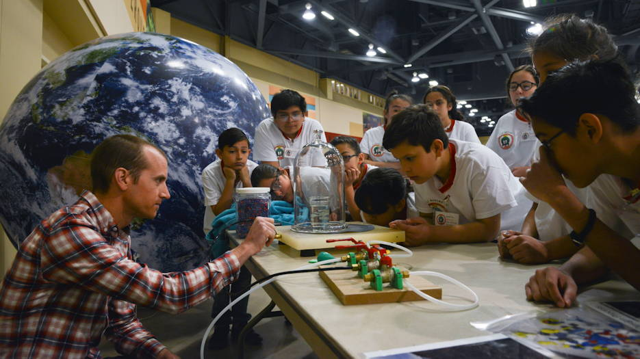 Zak Wilson, a mechanical engineer with Sandia National Laboratories, conducts experiments with air pressure for students during the 2019 Mission to Mars at the Albuquerque Convention Center May 10th. The Air Force Research Laboratory New Mexico's STEM Outreach branch put on the mission, with more than 1,300 fifth-grade students from schools across the Albuquerque area and New Mexico taking part in the massive science and engineering experiment. (U.S. Air Force photo by James Fisher)