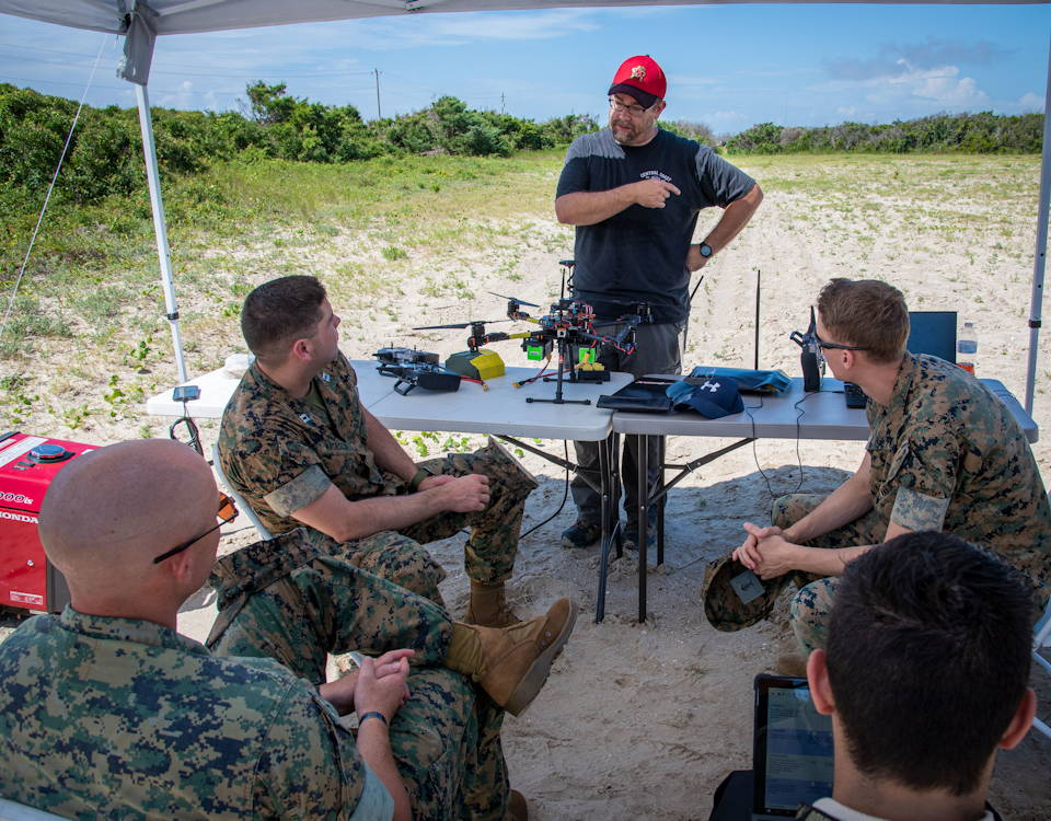 July 11, 2019 - Naval Information Warfare Center (NIWC) Atlantic employee Chad Sullivan discusses some of the capabilities of the Autonomous Swarming Aerial Payload (ASAP) Delivery System with an assessment team during the 21st Century Combined Arms Advanced Naval Technology Exercise (ANTX) East held at Marine Corps Base Camp Lejeune July 9-20. ANTX East is the fourth in a series of exercises designed to identify capability options for the warfighter aimed at addressing emerging operational requirements. (U.S. Navy photo by Joe Bullinger)