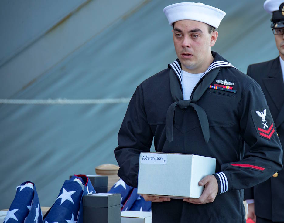 November 11, 2019 - Gunner's Mate 2nd Class Robert Ashman, from Virginia Beach, Virginia, assigned to USS Gerald R. Ford's (CVN 78) weapons department, carries his grandfather's, Chief Hull Maintenance Technician Dean Curtis Ashman, urn during a burial at sea ceremony on the ship's aircraft elevator three. Thirty souls were laid to rest during the first burial at sea ceremony held aboard Ford. (U.S. Navy photo by Mass Communication Specialist 3rd Class Connor Loessin)