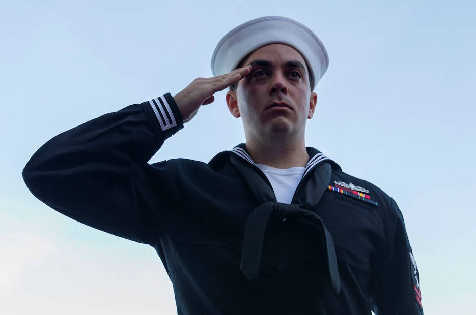 November 11, 2019 - Gunner's Mate 2nd Class Robert Ashman, from Virginia Beach, Virginia, assigned to USS Gerald R. Ford's (CVN 78) weapons department, salutes during a burial at sea ceremony on the ship's aircraft elevator three. Thirty souls were laid to rest during the first burial at sea ceremony held aboard Ford. (U.S. Navy photo by Mass Communication Specialist Seaman Apprentice Angel Thuy Jaskuloski)