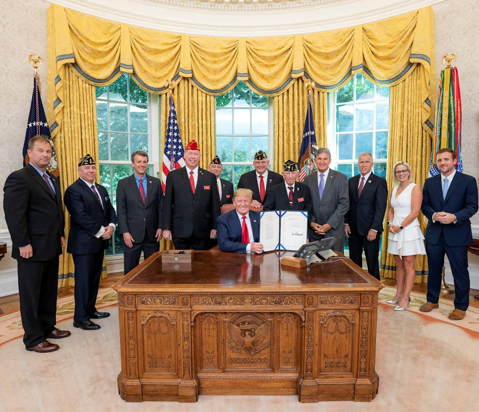 July 30, 2019 - President Donald J. Trump displays his signature after signing S. 504, the Let Everyone Get Involved in Opportunities for National Service (Legion) Act in the Oval Office of the White House that the veterans and elected officials around him proudly witnessed. (Official White House Photo by Tia Dufour)