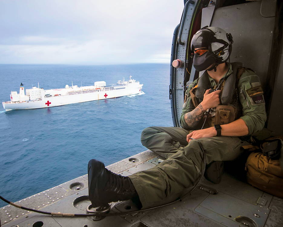 June 24, 2019 - Navy Petty Officer 2nd Class Matt Braaten looks out from an MH-60S Seahawk flying alongside the USNS Comfort in the Pacific Ocean. The Comfort is on a humanitarian mission to Central and South America and the Caribbean. (U.S. Navy photo by Petty Officer 2nd Class Nall Morgan K. Nall)