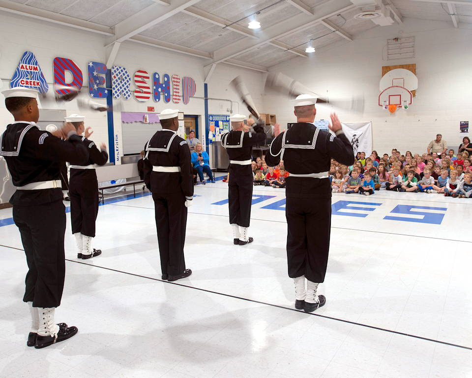 October 7, 2019 - A drill team assigned to the U.S. Navy Ceremonial Guard performs for students at Alum Creek Elementary School during Charleston Navy Week. The Navy Week program serves as the Navy's principle outreach effort in areas of the country without a significant Navy presence. (Image created by USA Patriotism! from U.S. Navy photo by Mass Communication Specialist 2nd Class Brenton Poyser)