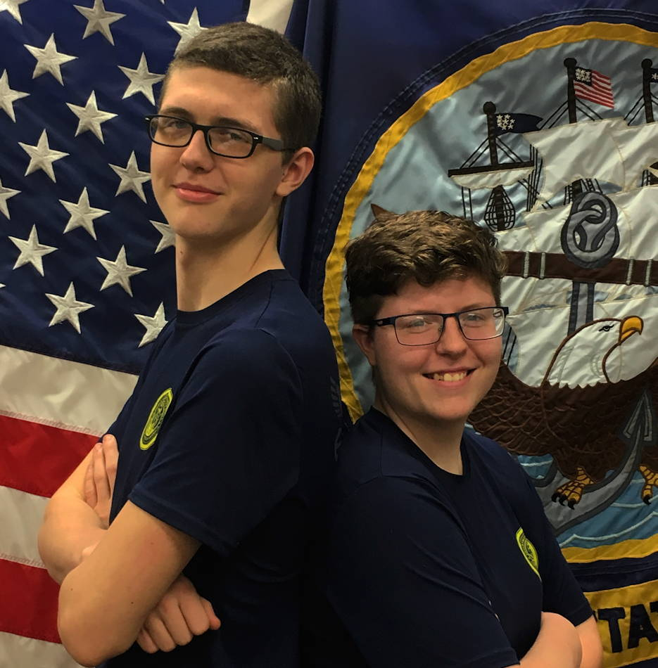 April 22, 2019 - Siblings, Hannah Craig and Cameron Cole, stand proudly together in front of the U.S and Navy flags after enlisting in the U.S. Navy together. (U.S. Navy photo by Hospital Corpsman 1st Class Caitlyn Strader)