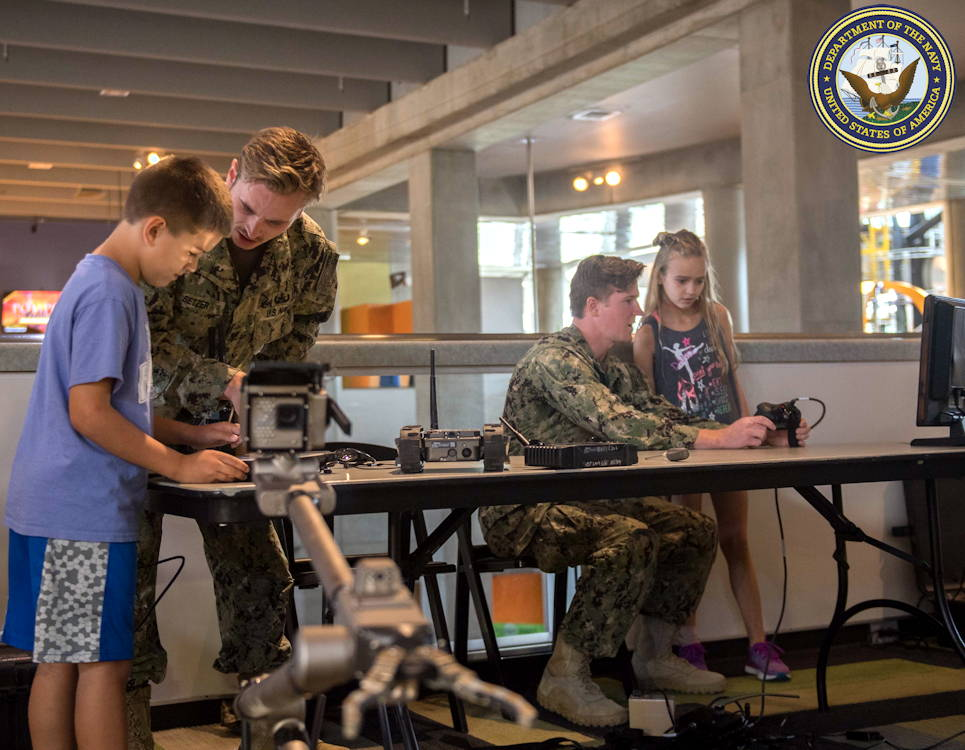 September 2, 2019 - Explosive Ordnance Disposal 3rd Class Austin Setzer, left, and Explosive Ordnance Disposal 3rd Class Sean Whitaker, right, (both assigned to U.S. Navy Explosive Ordnance Disposal Group 2) ... show kids how to use various bomb disposal robots at the St Louis Science Center, as part of St. Louis Navy Week. (Image created by USA Patriotism! from U.S. Navy photo by Mass Communication Specialist 2nd Class Abigayle Lutz)