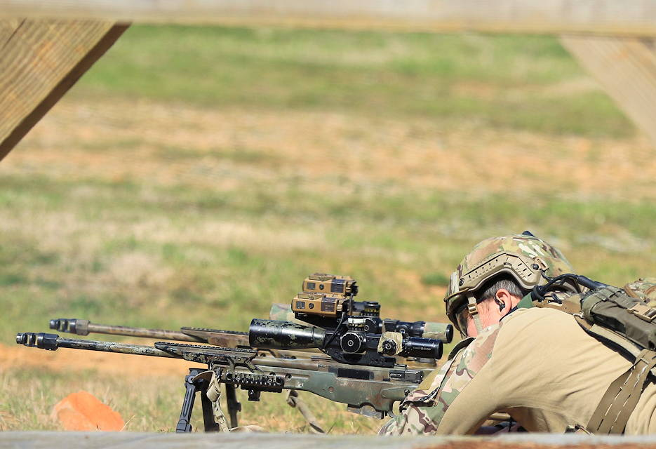 A competitor in the United States Army Special Operations Command International Sniper Competition looks through the scope of a sniper rifle on Fort Bragg, North Carolina, March 19, 2019. Twenty-one teams competed in the USASOC International Sniper Competition where instructors from the United States Army John F. Kennedy Special Warfare Center and School designed a series of events that challenged the two-person teams' ability to work together, firing range, speed and accuracy in varied types of environments. (U.S. Army photo by Sgt. Michelle Blesam)