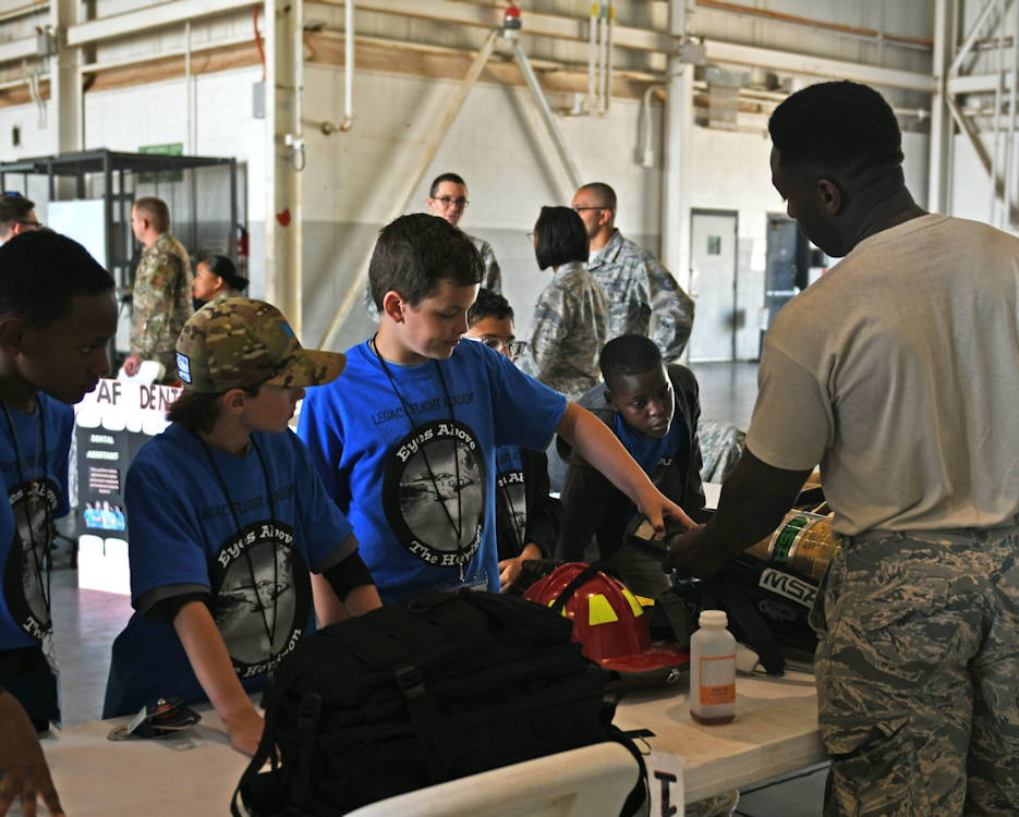 U.S. Air Force Staff Sgt. Anthony Bacoat, 7th Civil Engineering Squadron firefighter, explains the functions of firefighter equipment to students during the Eyes Above the Horizon event at Dyess Air Force Base, May 18, 2019. Students were exposed to a variety of civilian and military careers to encourage them to think about their future. (U.S. Air Force photo by Airman 1st Class Susan Roberts)