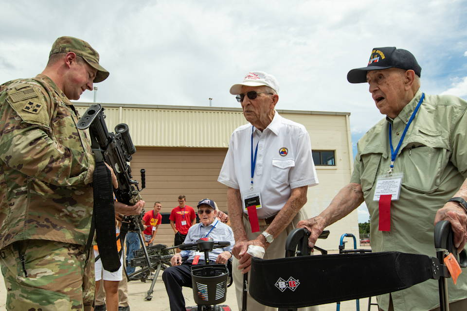 July 25, 2019 - Cpt. James Frederick, a Soldier assigned to Headquarters and Headquarters Company, 2nd Battalion, 23rd Infantry Regiment, 1st Stryker Brigade Combat Team, 4th Infantry Division, demonstrates modern weapons to World War II veterans who served with the 12th Armored (Hellcat) Division and their families, on Fort Carson Colorado on July 25, 2019. The 12AD colors fly proudly at the United States Holocaust Memorial Museum in Washington D.C., where it is among the divisions honored and recognized for taking part in the liberation of prisoners from Nazi concentration camps and other sites of incarceration. U.S. Army photo by Spc. Robert Vicens Rolon)