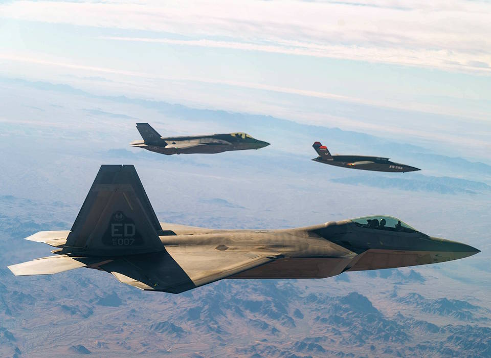 A U.S. Air Force F-22 Raptor and F-35A Lightning II fly in formation with the XQ-58A Valkyrie low-cost unmanned aerial vehicle over the U.S. Army Yuma Proving Ground testing range, Ariz., during a series of tests, Dec. 9, 2020. This integrated test follows a series of gatewayONE ground tests that began during the inaugural Department of the Air Force on-ramp last year in December. (U.S. Air Force photo by Tech. Sgt. James Cason)