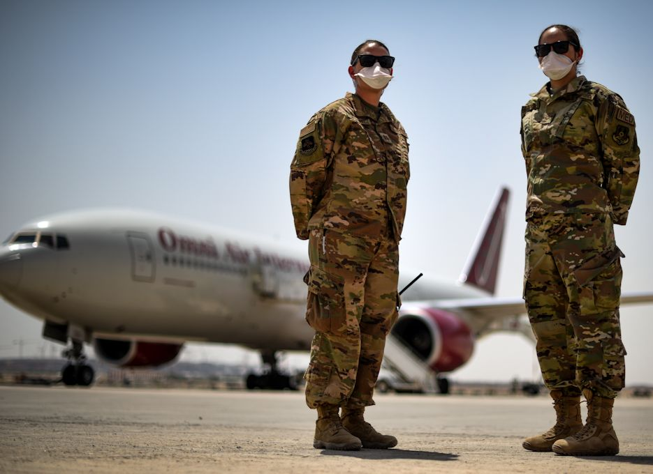 Capt. Stephanie Kompoltowicz, 386th EMDG Nurse and Senior Airman Lauren Frensley, 385th EMDG Flight Medical Technician pose for a portrait on the flightline of Cargo City, Kuwait, June 2, 2020. The 386th EMDG screens service members from multiple branches including the U.S. Air Force, U.S. Army and Marine Corps that come through Cargo City. (U.S. Air Force photo by Senior Airman Kevin Tanenbaum)