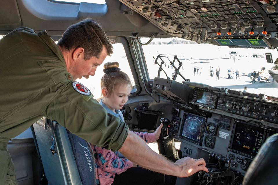 January 25, 2020 - U.S. Air Force Maj. Andrew Mazzarelli, a C-17 Globemaster III instructor pilot assigned to the 97th Air Mobility Wing, Altus Air Force Base, OK, demonstrates how to fly the aircraft to a young girl during the Aerospace and Aviation Day at Orlando Sanford International Airport, FL. (U.S. Air Force photo by Airman 1st Class Breanna Klemm)
