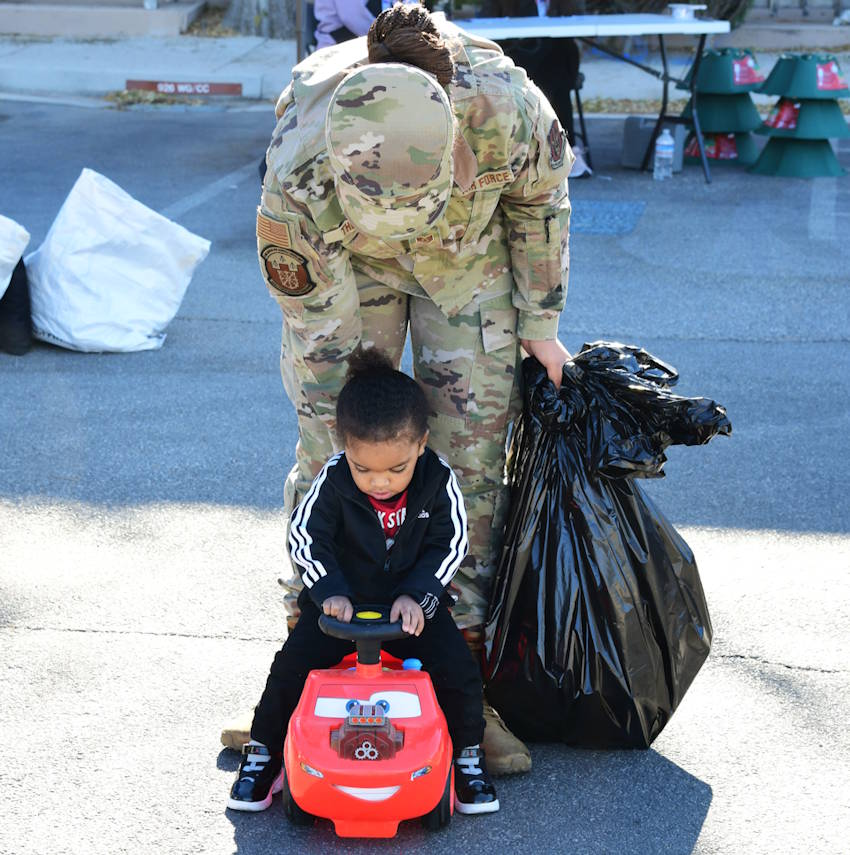 Staff Sgt. Tatianna Thomas, 926 Force Support Squadron services specialist, lets her son, Michael Johnson, take his new car for a ride during the Airman and Family Readiness Operation Holiday Hope event, Dec. 5, 2020, Nellis Air Force Base, Nevada. (U.S. Air Force Photo by Staff Sgt. Paige Yenke)