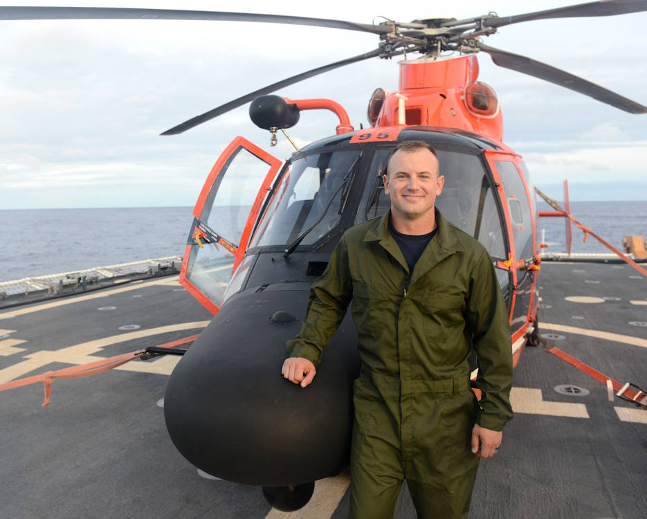 Fireman Lonnie Taber with an Air Station Barbers Point MH-65 Dolphin helicopter on the flight deck of the Coast Guard Cutter Kimball (WMSL 756) off Hawaii on March 12, 2020. Taber, an Iraq War Veteran, was leaving that night aboard the Dolphin to attend Aviation Maintenance Technician A-School. (U.S. Coast Guard photo by Petty Officer 2nd Class Matthew West)