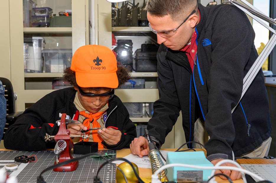 January 25, 2020 - U.S. Marine Corps Capt. Matthew Caspers, right, instructs a Boy Scout from the Boy Scouts of America how to solder electronic components onto a circuit board during a STEM-based merit badge event held on the Naval Postgraduate School campus, helping scouts from seven troops earn merit badges in topics such as weather, electronics, oceanography, robotics, electricity, programming, radio, and digital technology. (U.S. Navy photo by MC2 Nathan K. Serpico)