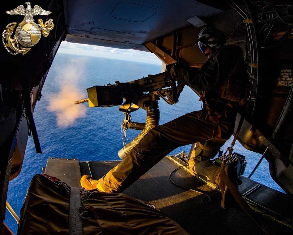 March 14, 2020 - A Marine with Marine Medium Tiltrotor Squadron (VMM) 265 (Reinforced), 31st Marine Expeditionary Unit (MEU), fires an M2 Browning .50 Caliber machine gun off of a CH-53E Super Stallion helicopter with VMM-265 (Rein.), 31st MEU, after departing amphibious assault ship USS America (LHA 6) in the South China Sea. (Image created by USA Patriotism! from U.S. Marine Corps photo by Cpl. Isaac Cantrell)