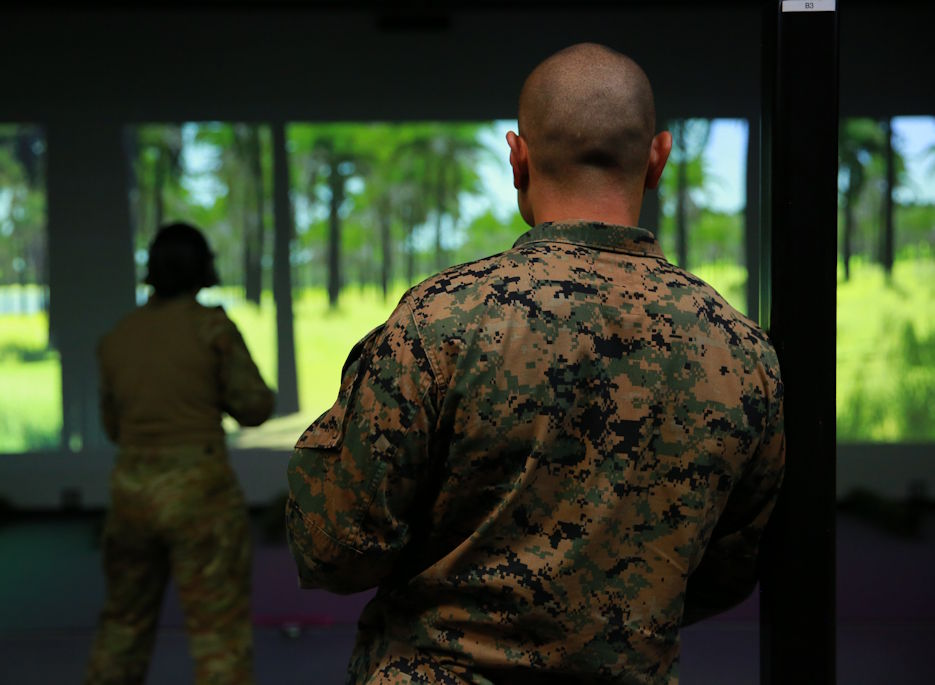 April 29, 2020 - U.S. Marine Corps Gunnery Sgt. Neilryan Sablan, the administration chief with Marine Rotational Force – Darwin, coaches U.S. Marines and Australian Defence Force service members through shooting the M4 carbine at Robertson Barracks in Darwin, Northern Territory, Australia, April 29, 2020. The Marine service rifle was integrated with the Australian's Weapons Training Simulation System for the first time, allowing the U.S. and Australian service members to maintain readiness while observing proper COVID-19 social distancing rules. The Marines were part a 54 member advance party who arrived prior to boarder closures associated with COVID-19. (U.S. Marine Corps photo by Lance Cpl. Natalie Greenwood)