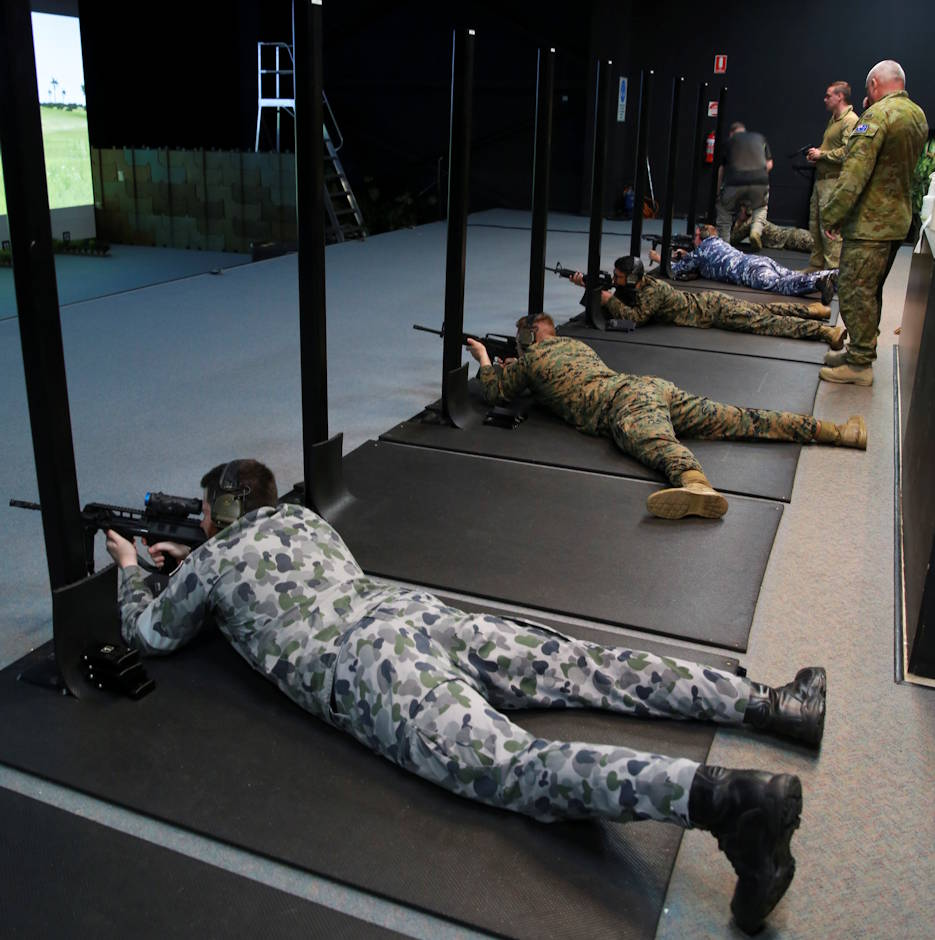 April 29, 2020 - U.S. Marines and Australian Defence Force service members shoot an M4 carbine on the Weapons Training Simulation System at Robertson Barracks in Darwin, Northern Territory, Australia. The Marine service rifle was integrated with the Australian's WTSS for the first time, allowing the U.S. and Australian service members to maintain readiness while observing proper COVID-19 social distancing rules. The Marines were part a 54 member advance party who arrived prior to boarder closures associated with COVID-19. (U.S. Marine Corps photo by Lance Cpl. Natalie Greenwood)