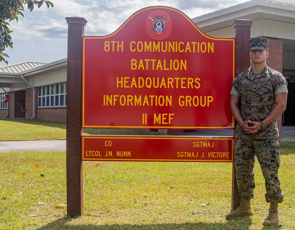 October 6, 2020 - U.S. Marine Corps Lance Cpl. Nicolas Gonzalez-Alzate, a radio operator with 8th Communication Battalion (8CB), II Marine Expeditionary Force Information Group, II Marine Expeditionary Force, proudly stands next to the 8CB headquarters sign on Camp Lejeune, NC. (Image created by USA Patriotism! from U.S. Marine Corps photo by Lance Cpl. Armando Elizald.)