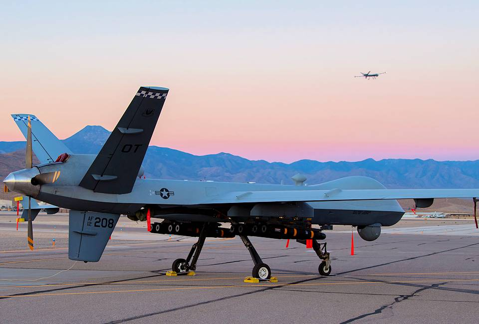 September 10, 2020 - An MQ-9A Reaper assigned to the 556th Test and Evaluation Squadron sits on the ramp at Creech Air Force Base carrying eight Hellfire missiles, as another MQ-9A Reaper flies in the background. This was the first flight test of the MQ-9 carrying eight Hellfire missiles. (U.S. Air Force photo by Senior Airman Haley Stevens)