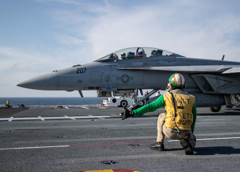 "March 19, 2020 - Chief Aviation Boatswain's Mate (Handling) Louis Mountain, from Seat Pleasant, Maryland, assigned to USS Gerald R. Ford's (CVN 78) air department, signals an F/A-18F Super Hornet, attached to ""Black Lions"" of Strike Fighter Squadron (VFA) 213, on Ford's flight deck during flight operations. Ford is currently underway conducting its flight deck and combat air traffic control center certifications. (U.S. Navy photo by Mass Communication Specialist 3rd Class Zachary Melvin)"