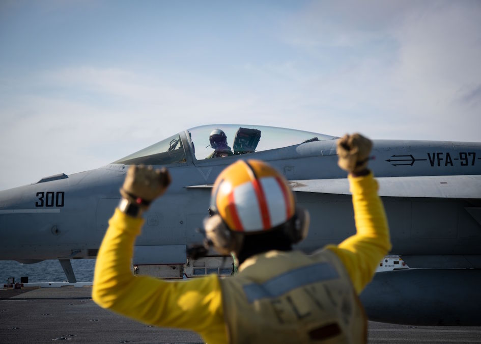 "March 19, 2020 - Aviation Boatswain's Mate (Handling) 1st Class Jawann Murray, from Detroit, assigned to USS Gerald R. Ford's (CVN 78) air department, signals an F/A-18F Super Hornet, attached to ""Black Lions"" of Strike Fighter Squadron (VFA) 213, on Ford's flight deck during flight operations. Ford is currently underway conducting its flight deck and combat air traffic control center certifications. (U.S. Navy photo by Mass Communication Specialist 3rd Class Zachary Melvin)"