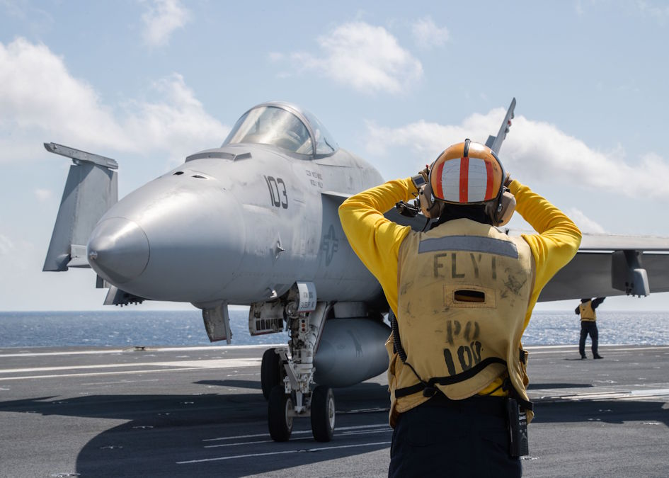 "March 19, 2020 - A Sailor assigned to USS Gerald R. Ford's (CVN 78) air department directs an F/A-18E Hornet, attached to ""Ragin' Bulls"" of Strike Fighter Squadron (VFA) 37, into place on USS Gerald R. Ford's (CVN 78) flight deck during flight operations. Ford is currently underway conducting its flight deck and combat air traffic control center certifications. (U.S. Navy photo by Mass Communication Specialist 3rd Class Zachary Melvin)"