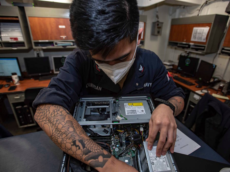October 9, 2020 - U.S. Navy Petty Officer 3rd Class Dean Caniban conducts maintenance on a computer in the automated data processing help desk center of the Navy's only forward-deployed aircraft carrier, the USS Ronald Reagan. (U.S. Navy photo by Petty Officer 3rd Class Quinton A. Lee)