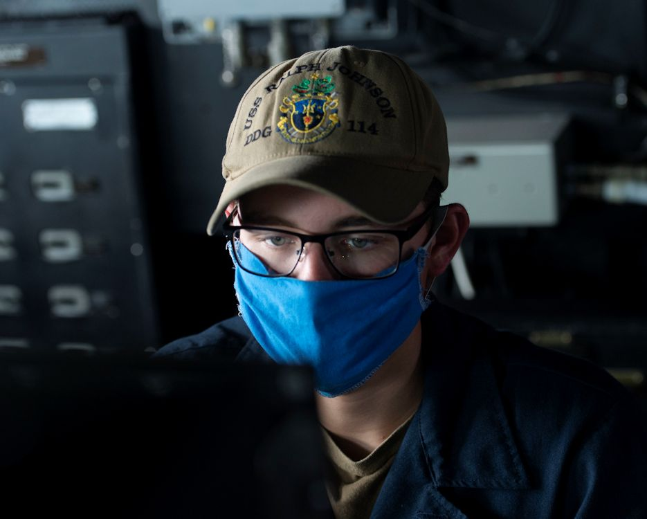 July 18, 2020 - Gunner's Mate Seaman Ian Delaughter, from Charleston, S.C., assigned to the Arleigh Burke-class guided-missile destroyer USS Ralph Johnson (DDG 114), mans a control station while transiting the Strait of Malacca. Ralph Johnson is part of the Nimitz Carrier Strike Group and is deployed conducting maritime security operations and theater security cooperation efforts. (U.S. Navy photo by Petty Officer 3rd Class Anthony Collier)