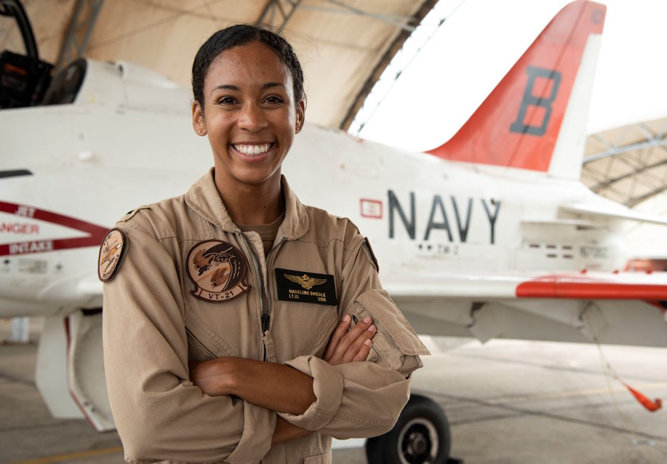 "July 17, 2020 - Lt. j.g. Madeline G. Swegle, the U.S. Navy's first Black female tactical jet aviator stands in front of a T-45C Goshawk jet trainer aircraft on the Training Air Wing 2 flight line at Naval Air Station Kingsville, Texas, July 17, 2020. Swegle completed her final training flight with the ""Redhawks"" of Training Squadron 21 and was soft winged July 7, 2020. (U.S. Navy photo by Lt. Michelle Tucker)"