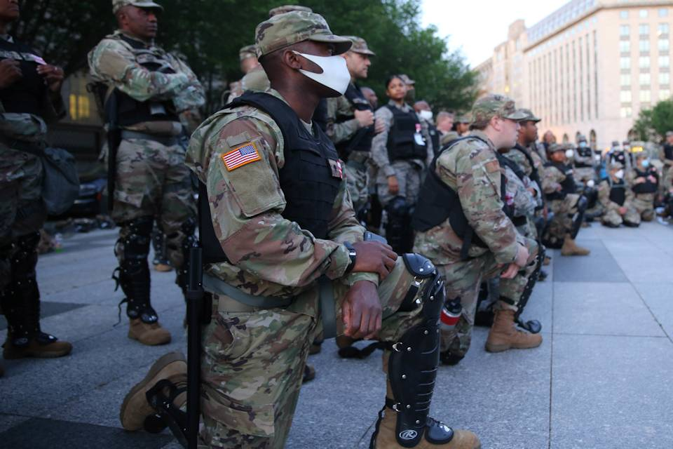 Soldiers, some kneeling and others standing, look ahead. (Photo By: Army National Guard photo by Staff Sgt. Tyrone Williams)