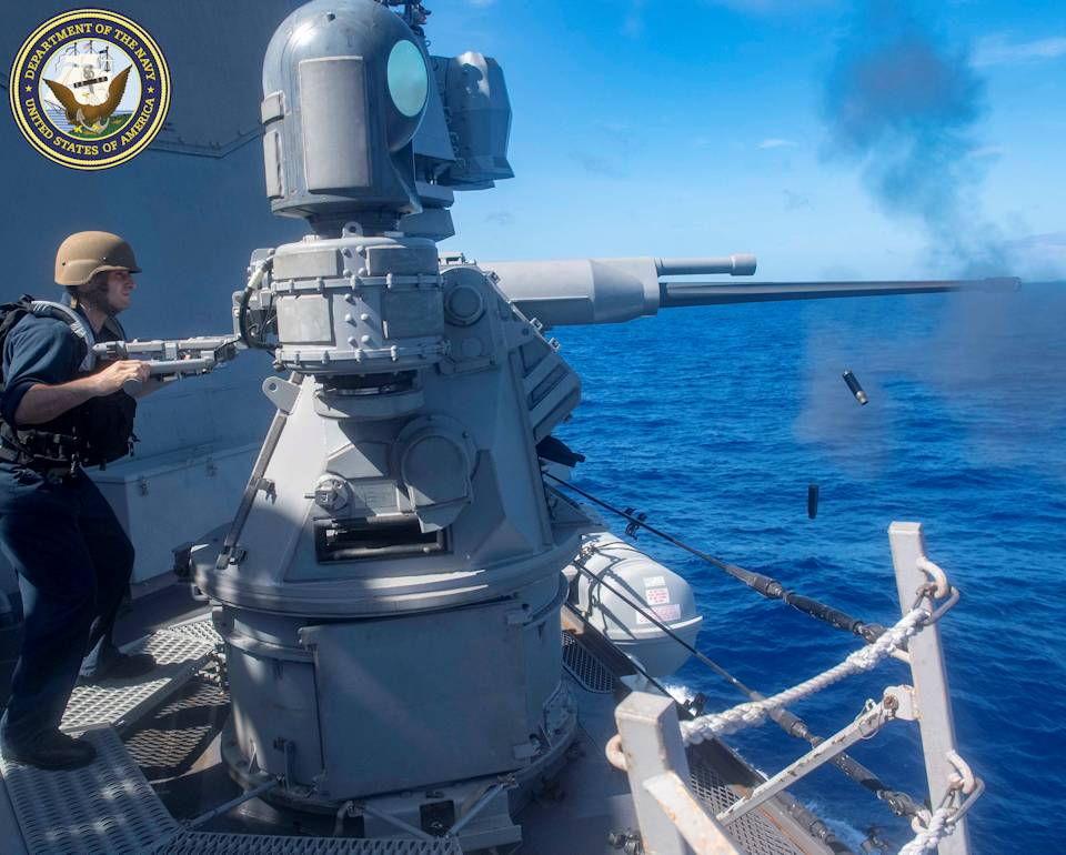 May 30, 2020 - A sailor fires a Mark 38 25mm machine gun system aboard the Arleigh Burke-class guided-missile destroyer USS Mustin (DDG 89) during a live-fire exercise. (Image created by USA Patriotism! from U.S. Navy photo by Mass Communication Specialist 3rd Class Cody Beam)