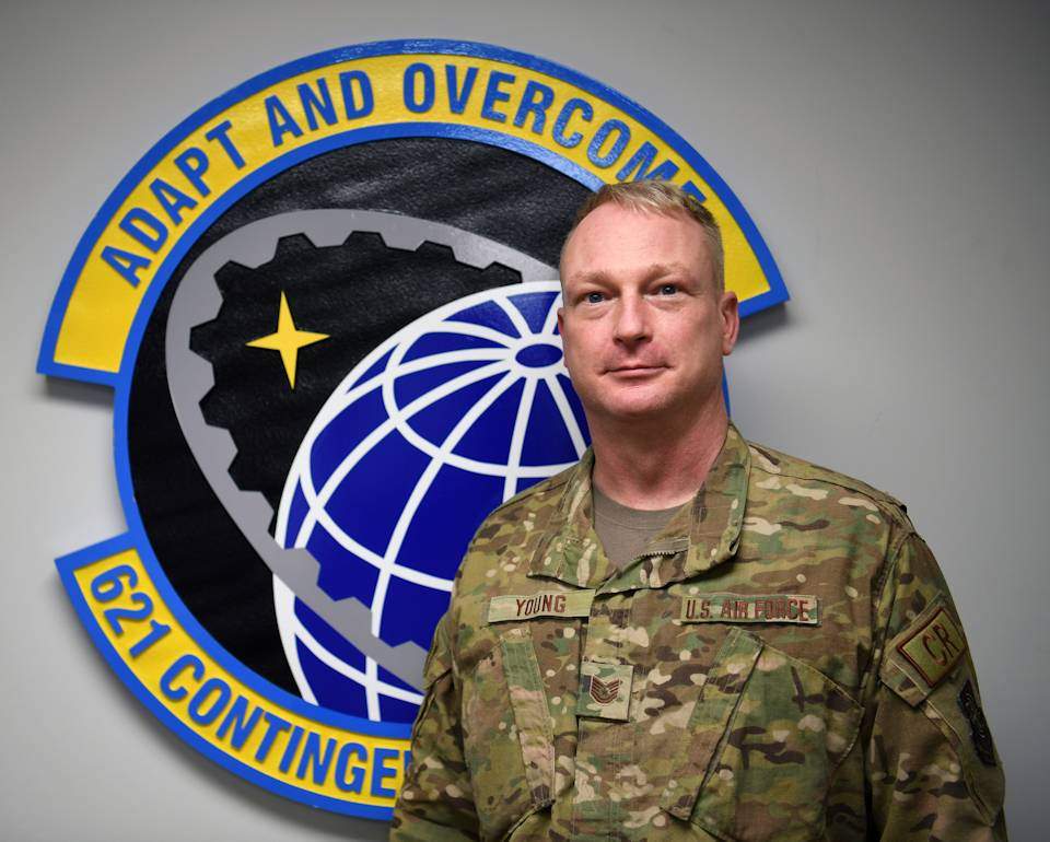 U.S. Air Force Tech. Sgt. Kelly Young, 621st Contingency Response Squadron self-inspection program manager, in front of his squadron emblem at Joint Base McGuire-Dix-Lakehurst, New Jersey on Jan. 13, 2021. Young is active around the base and in his squadron with various programs that help Airmen and their families. (U.S. Air Force photo by Tech. Sgt. Luther Mitchell Jr.)