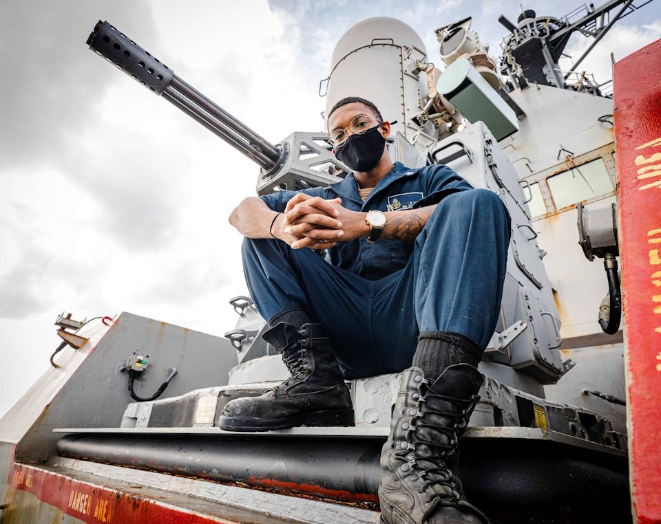 January 20, 2021 - Fire Controlman 2nd Class Dondre Summers, from Waldorf, Md., sits on a Close-In Weapons System (CIWS) mount on the foc's'le aboard the Arleigh Burke-class guided-missile destroyer USS John S. McCain (DDG 56). McCain is assigned to Destroyer Squadron (DESRON) 15, the Navy's largest forward-deployed DESRON and the U.S. 7th Fleet's principal surface force. (U.S. Navy photo by Mass Communication Specialist 2nd Class Markus Castaneda)