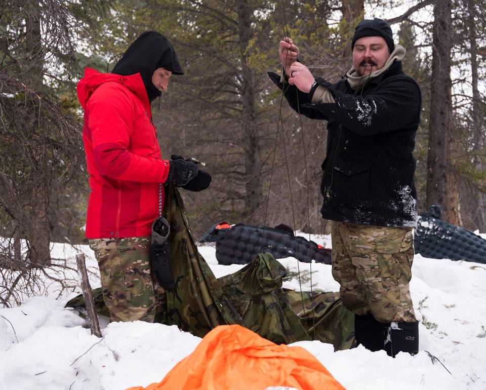 U.S. Air Force Maj. Jordan Wilke, pilot, 120th Fighter Squadron, and Master Sgt. Eric Maertens, Survival, Evasion, Resistance and Escape trainer, 140th Operations Support Squadron, prepare a shelter during SERE arctic training in San Isabel National Forest near Leadville, Colorado on February 9, 2021.(U.S. Air National Guard photo by Staff Sgt. Austin Harvill)