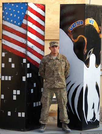 Staff Sgt. John Reyes, 2nd Special Troops Battalion, 2nd Brigade Combat Team, 4th Infantry Division of Eagle Pass, Texas, stands in front of painted two wooden towers to commemorate the 10th anniversary of the attacks on the World Trade Center on Sept. 1, 2011. Reyes painted an American flag and angel on the towers to memorialize the heroes and those who passed on Sept. 11, 2001. U.S. Army photo by Capt. Bonnie Hutchinson