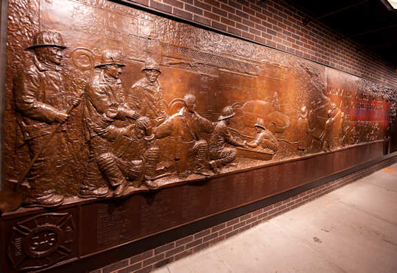 A bronze relief sculpture is displayed on the wall outside of Ladder 10 located at the southwest corner of the World Trade Center. The sculpture honors the 343 New York firefighters who lost their lives in the attack on the World Trade Center. Photo by Timothy Hale on August 20, 2011