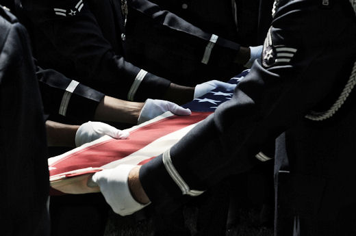 A United States Air Force Honor Guard body bearer team folds the U.S. flag during a full-honors funeral ceremony at Arlington National Cemetery. Honor Guard body bearers train constantly to maintain the precision they are known for. Their standards of flawlessness are set out of necessity to honor fallen Airmen. U.S. Air Force photo/Senior Airman Sean Adams