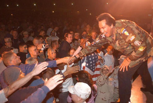 Wayne Newton greeting the troops during a performance for them.
