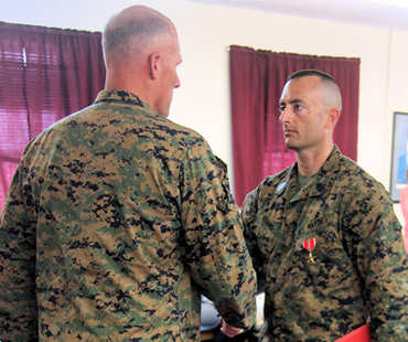 1st Sgt. Chis J. Adams, right, the company first sergeant for Fox Company, Battalion Landing Team, 2nd Battalion, 2nd Marine Regiment, 22nd Marine Expeditionary Unit, shakes hands with Brig. Gen. Christopher S. Owens, the deputy commanding general of II Marine Expeditionary Force, after receiving his Bronze Star Medal with Combat Distinguishing Device during an awards ceremony aboard Marine Corps Base Camp Lejeune, N.C., Feb. 25, 2011. Adams received his award for heroic actions while deployed to Afghanistan in 2010.