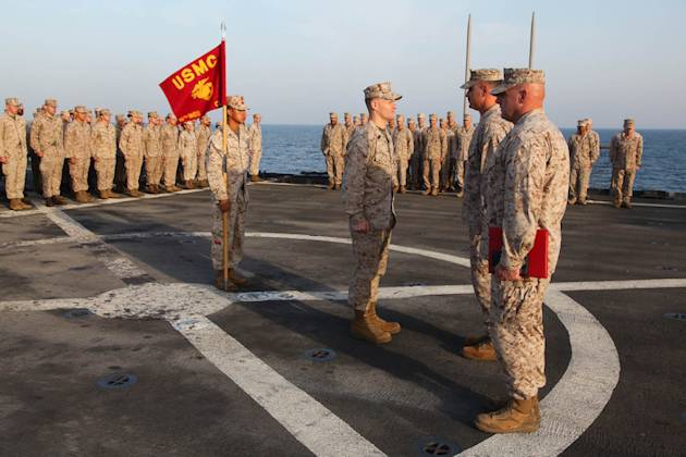 First Sgt. Bradley G. Simmons (center), Sergeant Major, Combat Logistics Battalion 15, 15th Marine Expeditionary Unit, stands in front of Lt. Col. John Wiener, commanding officer, CLB-15, 15th MEU, before being presented the Bronze Star with Combat Distinguishing Device, aboard the USS Rushmore, Jan. 25, 2013. (U.S. Marine Corps photo by Cpl. Timothy R. Childers)