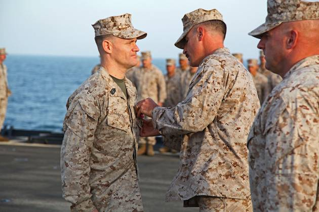 Lieutenant Col. John Wiener, commanding officer, Combat Logistics Battalion 15, 15th Marine Expeditionary Unit, pins the Bronze Star with Combat Distinguishing Device on 1st Sgt. Bradley G. Simmons (34), Sergeant Major, CLB-15, 15th MEU, during his award ceremony aboard the USS Rushmore, Jan. 25, 2013. The 15th MEU is deployed as part of the Peleliu Amphibious Ready Group as a U.S. Central Command theater reserve force, providing support for maritime security operations and theater security cooperation efforts in the U.S. 5th Fleet area of responsibility. (U.S. Marine Corps photo by Cpl. Timothy R. Childers)