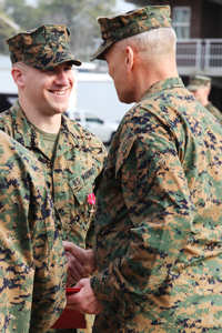 Cpl. John D. Carney, who served as a fire team leader with 1st squad, 3rd platoon, Fox Company, 2nd Battalion, 2nd Marine Regiment, Regimental Combat Team 7 in Afghanistan, receives a Bronze Star Medal with Combat Distinguishing Device from Lt. Gen. John M. Paxton, commanding general, II Marine Expeditionary Force, during a ceremony aboard Marine Corps Base Camp Lejeune, Feb. 28, 2011.