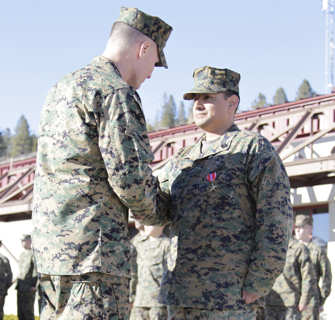 Master Sgt. Luis A. Carrillo shakes hands with Col. Phillip Chandler, the commanding officer of Marine Corps Mountain Warfare Training Center Bridgeport, after receiving a Bronze Star Medal for heroic combat service in Afghanistan Feb. 1, 2011, at the centers command post.