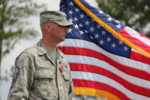 Master Sgt. Gene Jameson, III, stands proudly in front of the U.S. flag at Robins Air Force Base, Ga., Aug. 23, 2012. Jameson was awarded the Bronze Star medal for his actions while deployed to Bagram, Afghanistan. He battled a fire started by an insurgent's 107-millimeter rocket. U.S. Air Force photo by Robert Talenti