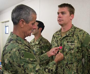 Rear Adm. Michael Tillotson, commander, Navy Expeditionary Combat Command presents the Bronze Star Medal to Explosive Ordnance Disposal Technician 2nd Class John F. Piowaty during an award ceremony at Explosive Ordnance Disposal Mobile Unit 2 on Joint Expeditionary Base Little Creek-Fort Story (JEBLC-FS), June 18, 2013. Piowaty was awarded the Bronze Star for meritorious achievement for combat operations as team leader while assigned to a joint task force in support of Operation Enduring Freedom in Afghanistan. (U.S. Navy photo by Mass Communication Specialist 3rd Class Randy Savarese)