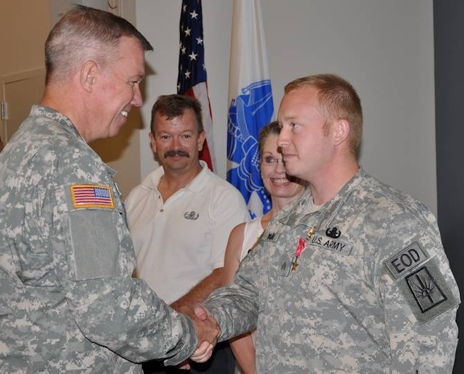 U.S. Army Brig. Gen. Michael Swezey, left, the commander of the 53rd Troop Command, New York Army National Guard congratulates Sgt. Joshua Young after he receives the Bronze Star with V device for valor during a ceremony at the Scotia-Glenville Armed Forces Reserve Center in Glenville, N.Y., July 19, 2013. Young was recognized for saving the life of a fellow Soldier while under continuous enemy fire March 16, 2012, in Afghanistan with an Explosive Ordnance Disposal battalion from Fort Drum, N.Y. Young is assigned to the 1108th Ordnance Company (Explosive Ordnance Disposal). (U.S. Army National Guard photo by Master Sgt. Corine Lombardo)
