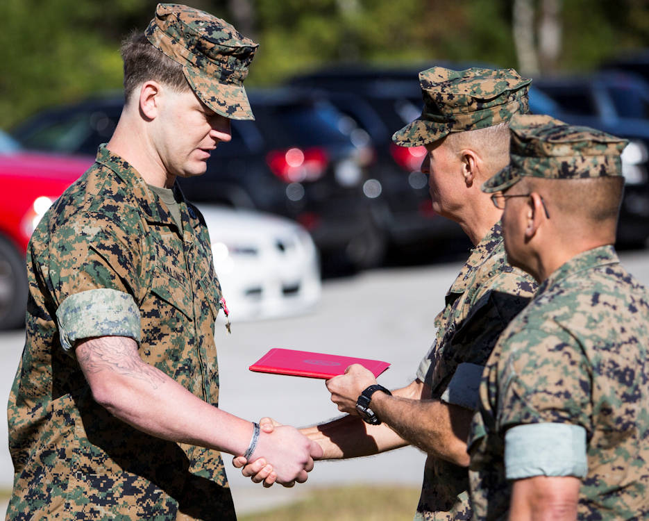 "October 30, 2017 - Maj. Gen. Carl E. Mundy III, U.S. Marine Corps Forces, Special Operations Command commander, awards the Bronze Star Medal with Combat ""V"" to Staff Sgt. Patrick H. Maloney, multi-purpose canine handler with 2D Marine Raider Battalion, at Camp Lejeune, North Carolina. While deployed in support of Operation Inherent Resolve in August 2016, Maloney exposed himself to enemy fire to employ a heavy machinegun mounted in an open truck bed during an enemy ambush. Despite two weapon malfunctions, Maloney effectively suppressed and disrupted the ambush, allowing Raiders to repel the attackers. Maj. Gen. Mundy presented the award on behalf of the President. (U.S. Marine Corps photo by Sgt. Salvador R. Moreno)"