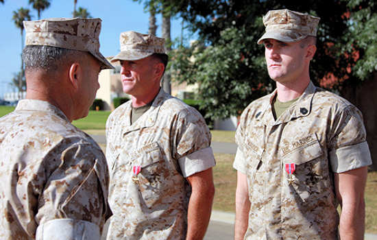 Maj. Christopher W. Rogers, team leader, 3d Civil Affairs Group, I Marine Expeditionary Force, and Gunnery Sgt. Christian W. Murdock, team chief, 3d CAG, are presented with the Bronze Star by Col. Paul Lebidine, commanding officer for 3d CAG, July 1, 2011. The Marines received the awards for multiple operations which resulted in a reduced ability to fund insurgent operations through a decline of enemy activity and increased security in support of Operation Enduring Freedom. Courtesy Photo